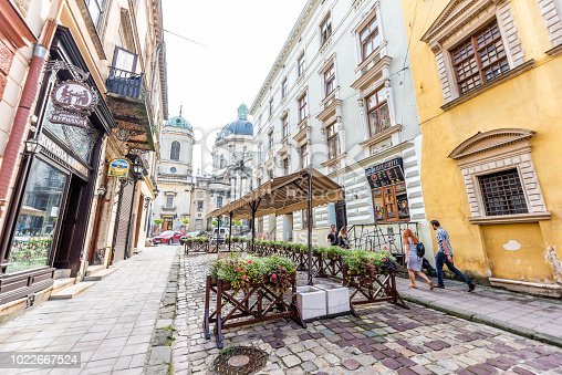 istock Dominican church cityscape streetscape with dome in historic Ukrainian Polish Lvov city during day, outdoor cafe restaurant, buildings, alley street in old town 1022667524