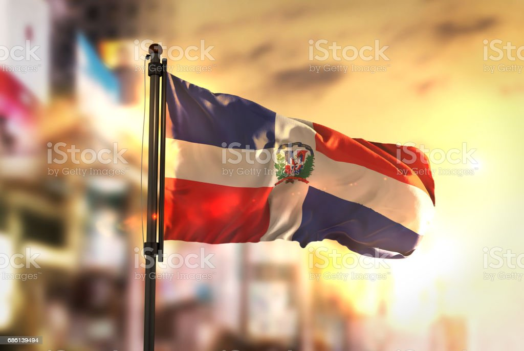 Dominican Republic Flag Against City Blurred Background At Sunrise Backlight
