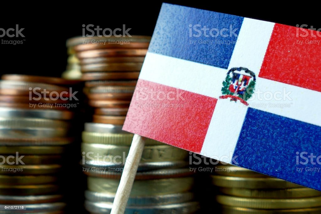 Dominican Republic flag waving with stack of money coins macro stock photo