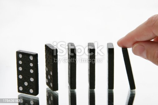 istock domino effect, knocking it down 175426183