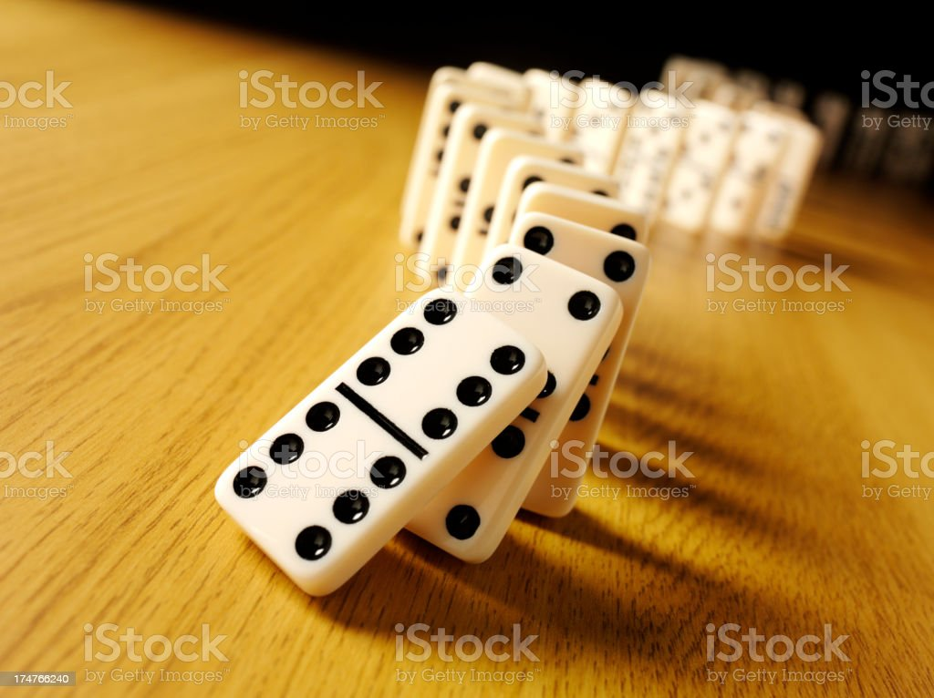 Domino Effect with Donimoes on a wooden Table stock photo