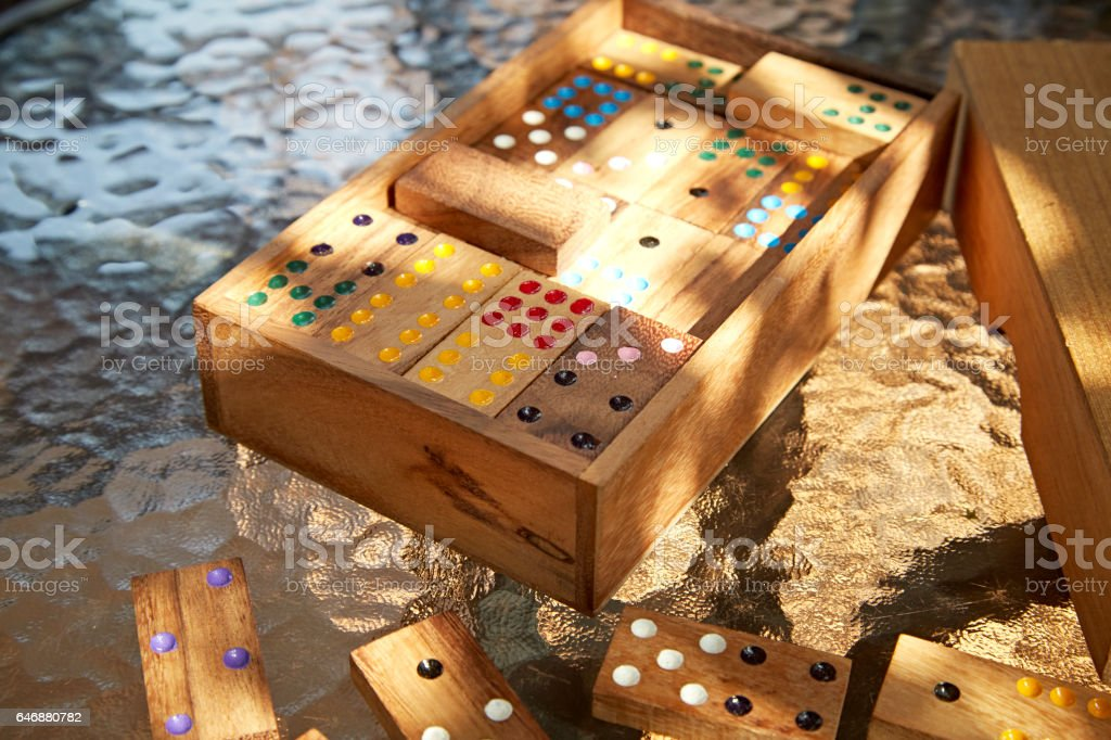 Wood domino game on glass table, daylight