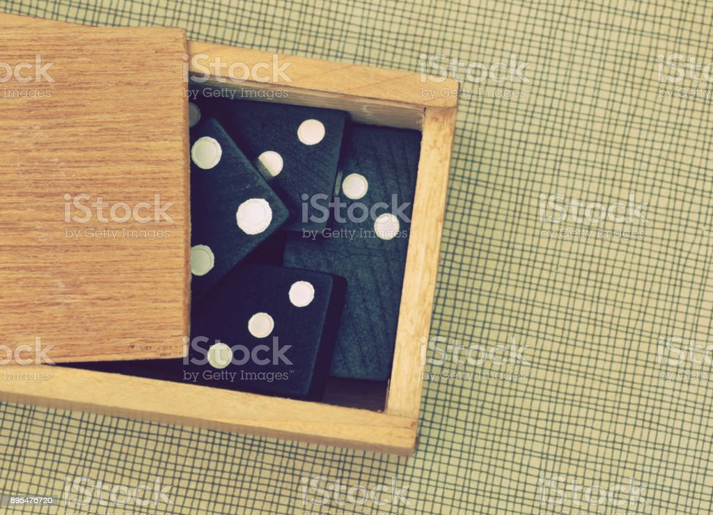 domino pieces in wooden box