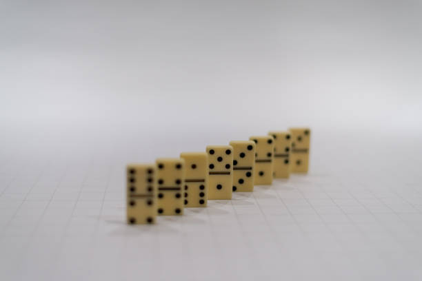 Domino pieces in row with middle one focused stock photo