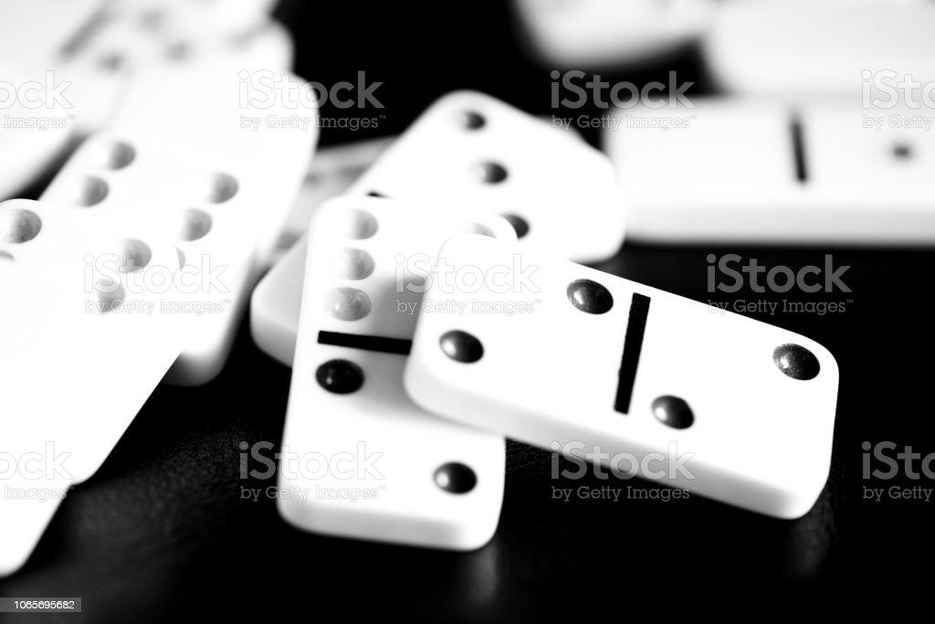 Fichas de dominó se encuentran dispersos en una superficie oscura cerca. Blanco y negro - foto de stock
