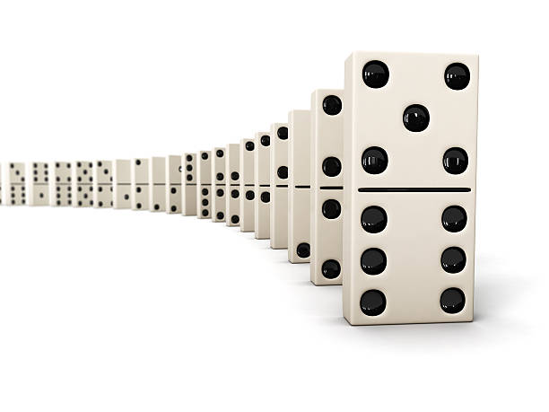 Dominoes lined up in a row against a white background stock photo