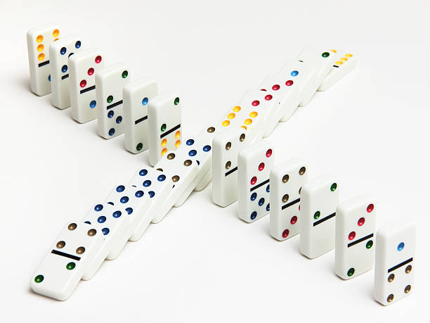 Dominoes on white background -  standing and fallen stock photo