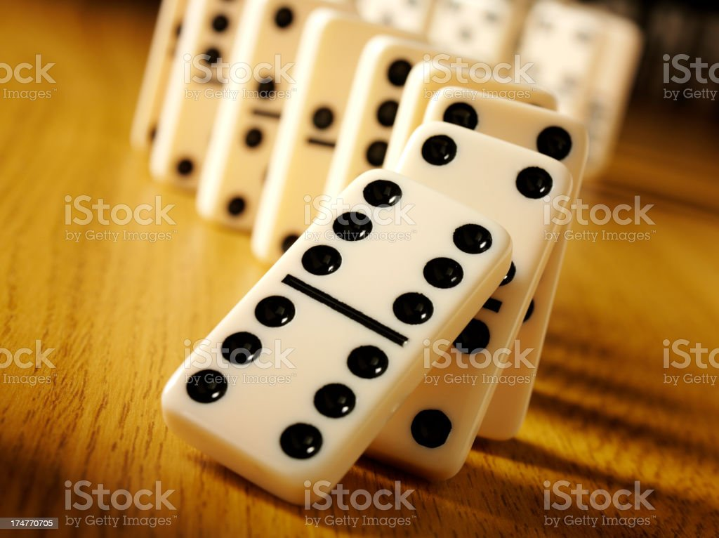 Dominoes with the domino effect on a wooden background with copy...