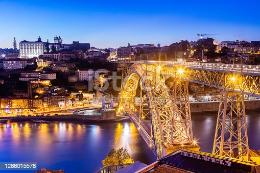 The Ribeira or riverside in Porto with Luís I Bridge seen accross the Douro river with restaurants and tourists along the riverbank seen illuminated at evening dusk, a popular tourist destination and one of UNESCO's World Heritage Sites.
