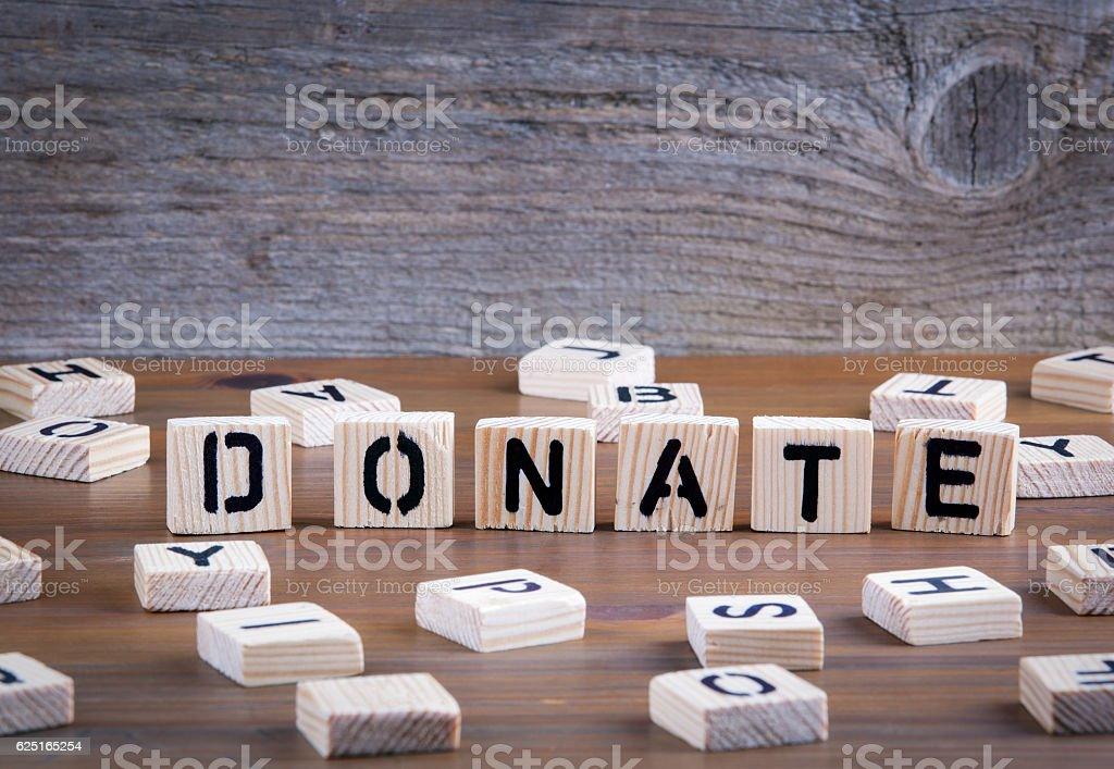 Donate from wooden letterson on wooden background stock photo