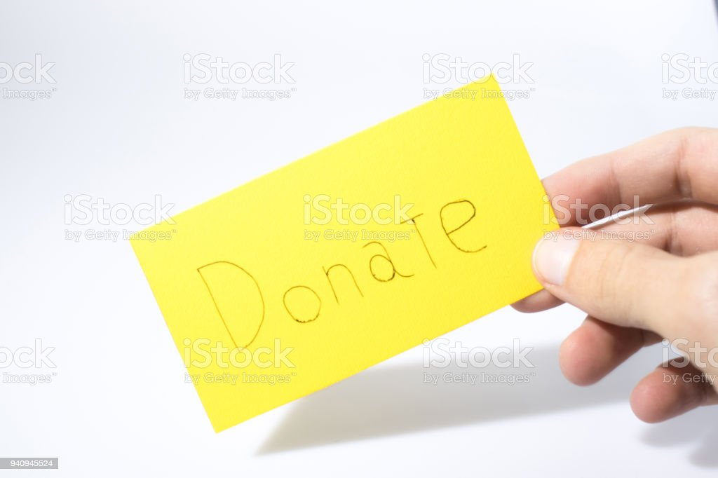 Donate handwrite witha a hand on a yellow paper composition stock photo
