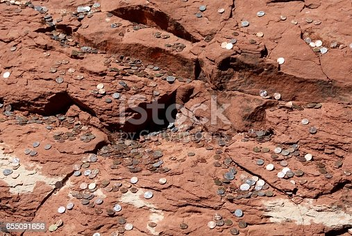 Donated coins thrown onto the rocks as the Chapel of the Holy Cross in Sedona Arizona