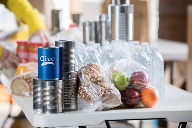 Donated food items on a table during food drive Donated fruit, bread and canned food item are on a table in a food bank. A can containing cash donations is on the table as well. food drive stock pictures, royalty-free photos & images