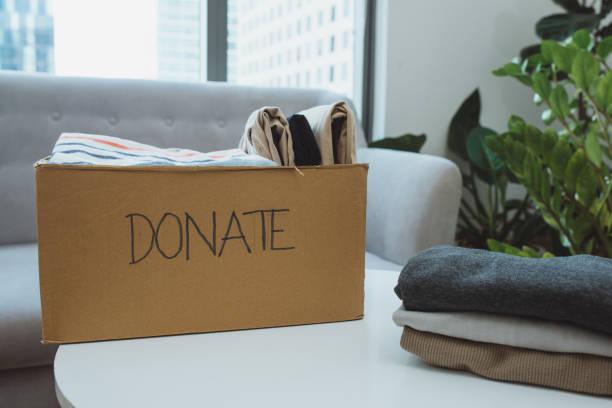 boîte de don et vêtements occasionnels dans le salon - équipement domestique photos et images de collection