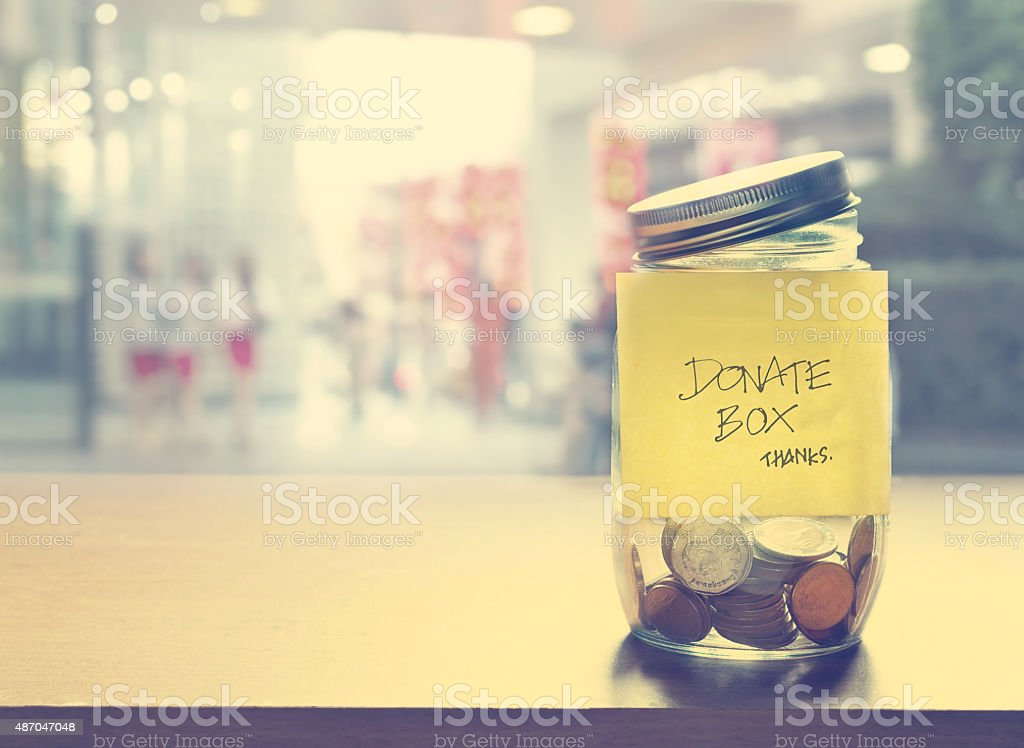 Donation box, coin in the glass bottle, vintage color tone stock photo