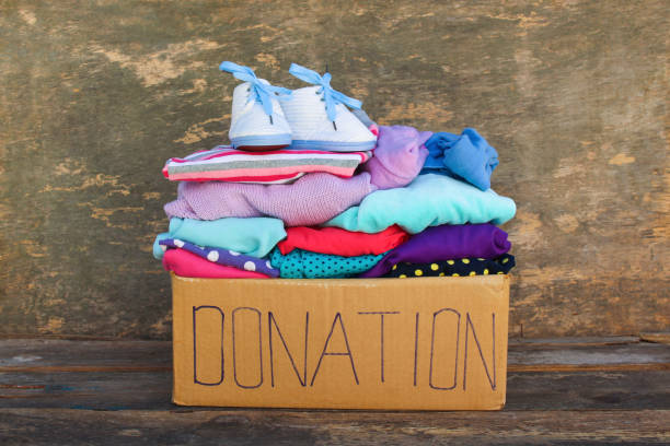 Donation box with children's things on wooden background. Donation box with children's things on wooden background. coat garment stock pictures, royalty-free photos & images