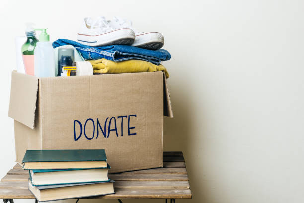 CLOTHES DONATION AND FOOD DONATION CONCEPT. Donation box with clothes and hygiene products. Copy space CLOTHES DONATION AND FOOD DONATION CONCEPT. Donation box with clothes and hygiene products. Copy space clothes in box stock pictures, royalty-free photos & images