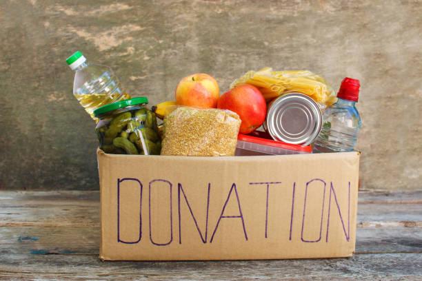 donation box with food on old wooden background - cassetta per le offerte foto e immagini stock