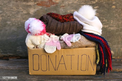 Donation box with warm winter clothes on old wooden background.