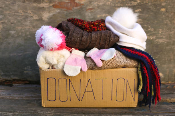 donation box with warm winter clothes on old wooden background. - mitene imagens e fotografias de stock