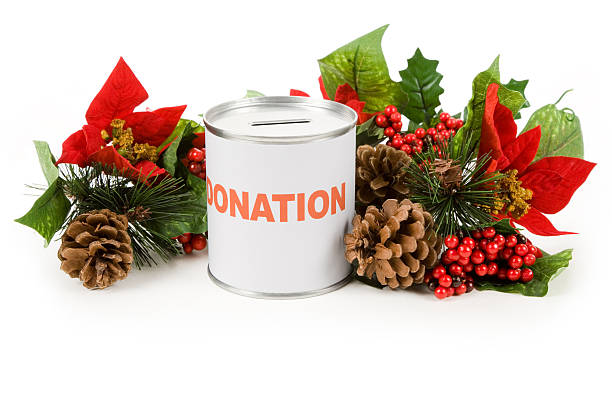 Donation can with Christmas poinsettia bouquet on white stock photo