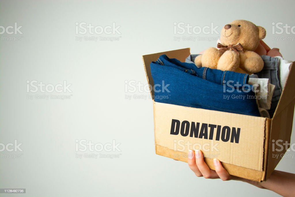 Donation concept. Hands holding donate box with clothes. Copy space. stock photo