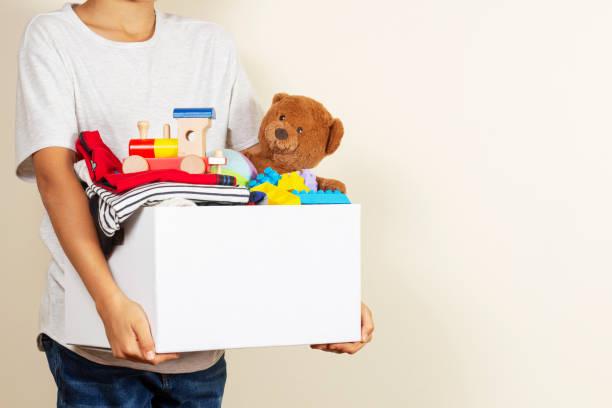 Spendenkonzept. Kinderhände halten Spendenbox mit Büchern, Kleidung und Spielzeug – Foto