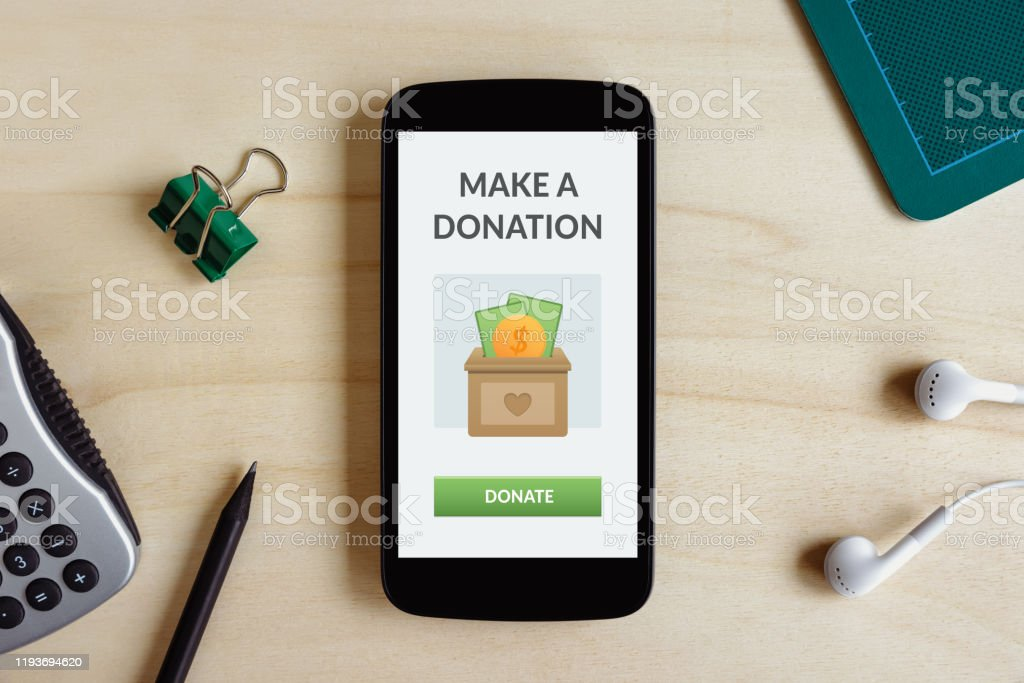 Donation concept on smart phone screen Donation concept on smart phone screen on wooden desk. Top view Altruism Stock Photo