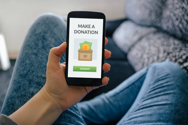 Donation concept Girl holding smart phone with donation concept on screen charitable donation stock pictures, royalty-free photos & images