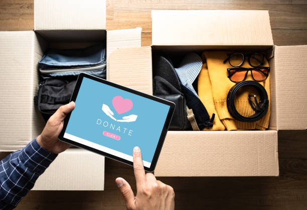 Donation concepts with young person packing accessories clothing and using digital tablet for donate.giving and sharing with human.second hand or recycle stock photo