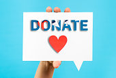 istock Donation, crowdfunding and hand help concept with heart shape on speech bubble and blue background. 1173012262