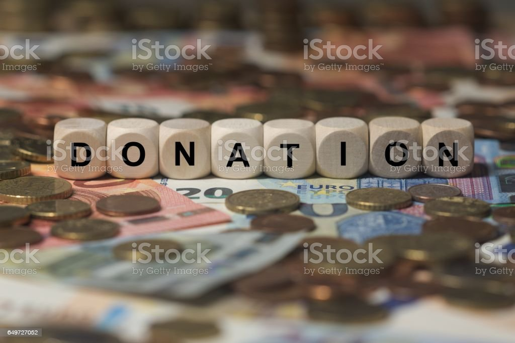 donation - cube with letters, money sector terms - sign with wooden cubes stock photo