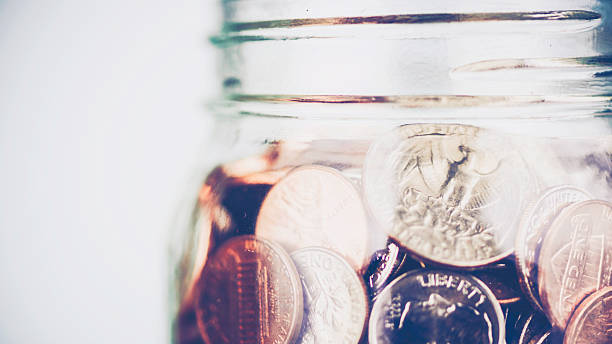 Donation jar overflowing with American money. Fundraising, Savings, Wealth Concepts. Donation jar overflowing with American money. Fundraising, Savings, Wealth Concepts. 401k stock pictures, royalty-free photos & images