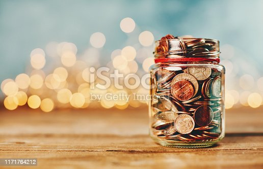 istock Donation money jar filled with coins in front of holiday lights 1171764212