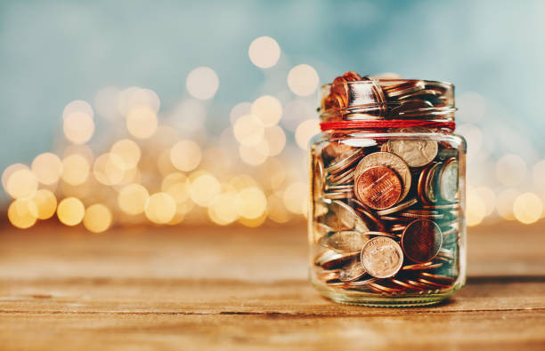 Donation money jar filled with coins in front of holiday lights Donation money jar filled with coins in front of holiday lights currency stock pictures, royalty-free photos & images