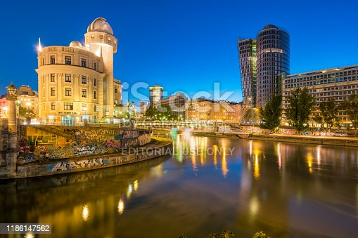 Donaukanal or Danube Canal riverside with the Urania Observatory in downtown Vienna Austria at twilight blue hour.