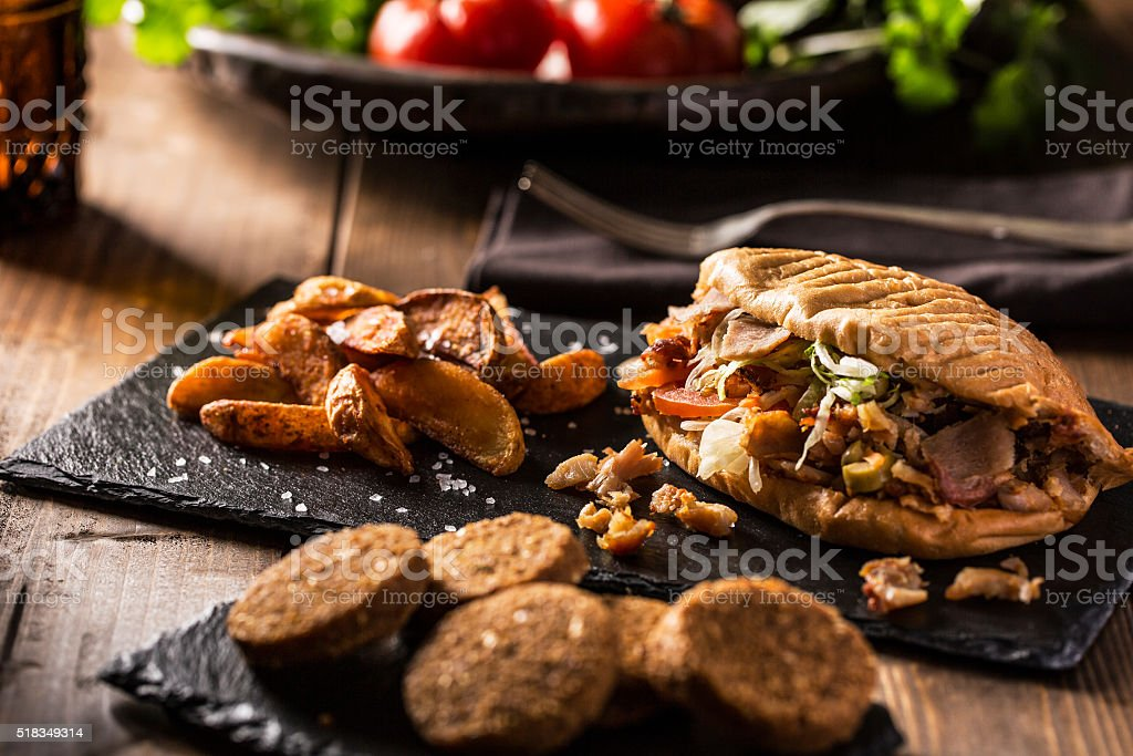 Doner kebab with fried potato on table stock photo