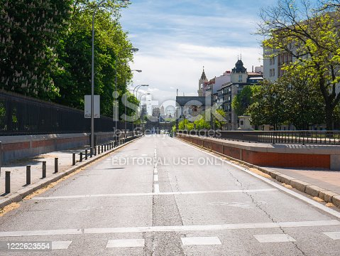Madrid, Spain, 05/01/2020: O`Donnell street, next to the Retiro Park, completely empty due to the state of alarm due to coronavirus with Puerta de Alcala in the background with a large black ribbon