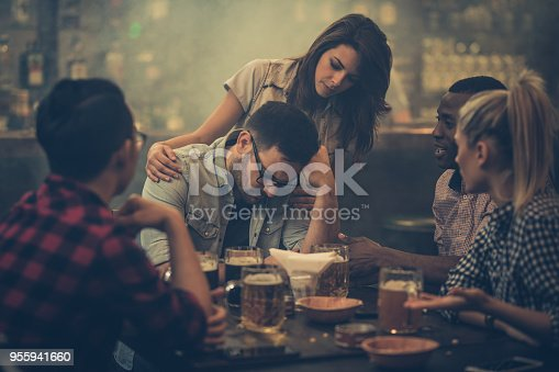 Group of friends consoling their friend who is sitting displeased in a bar.