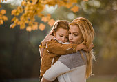 Affectionate mother consoling her little girl during autumn day in nature.