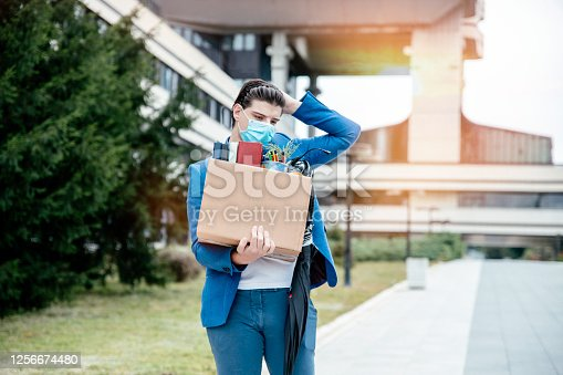 Stressed Millenial Man carrying carton box with office stuff replacing the job due to Coronavirus crisis.  Fired Businessman in front of office building with card box. copy space
