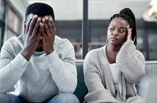 Shot of a young couple ignoring each other after having an argument on the sofa at home