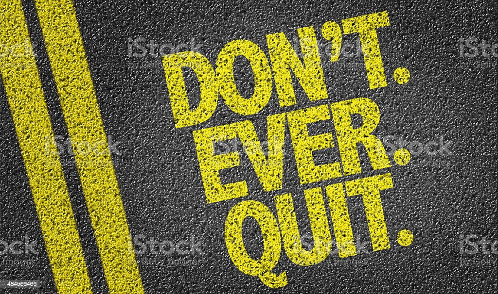 Dont. Ever. Quit. written on the road stock photo