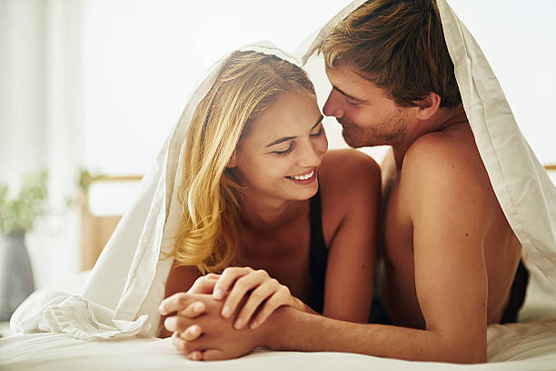 I don't ever want to leave this room Shot of a young couple sharing an intimate moment under the covers in bed real couples making love stock pictures, royalty-free photos & images