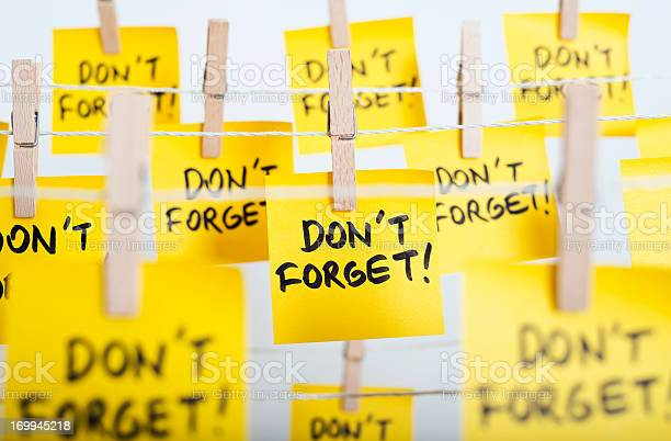 """adhesive note papers with """"don't forget!"""" message hanging on the rope"""