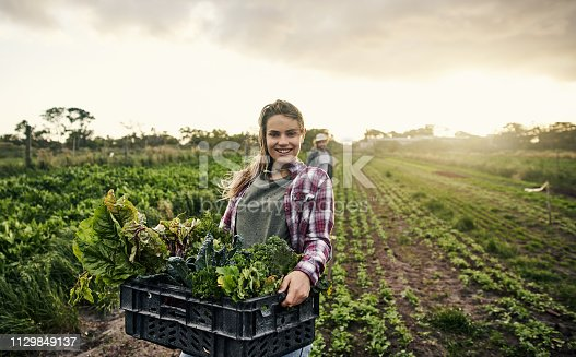 Shot of a young woman holding a crate of freshly picked produce on a farm