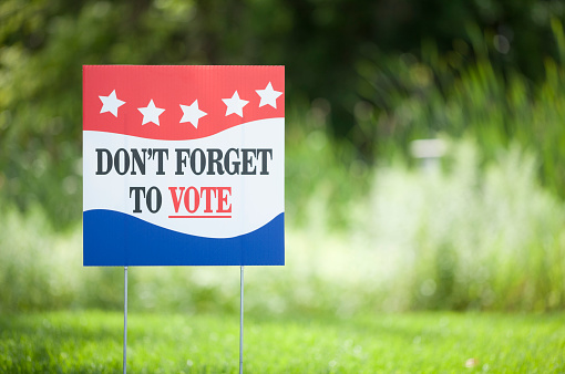 Presidential election don't forget to vote signage in front of a grassy field