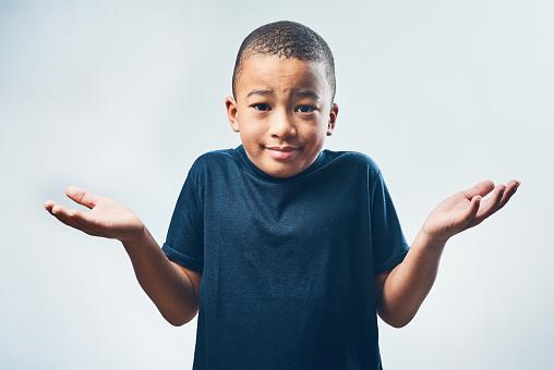 Studio shot of a cute little boy shrugging his shoulders against a grey background