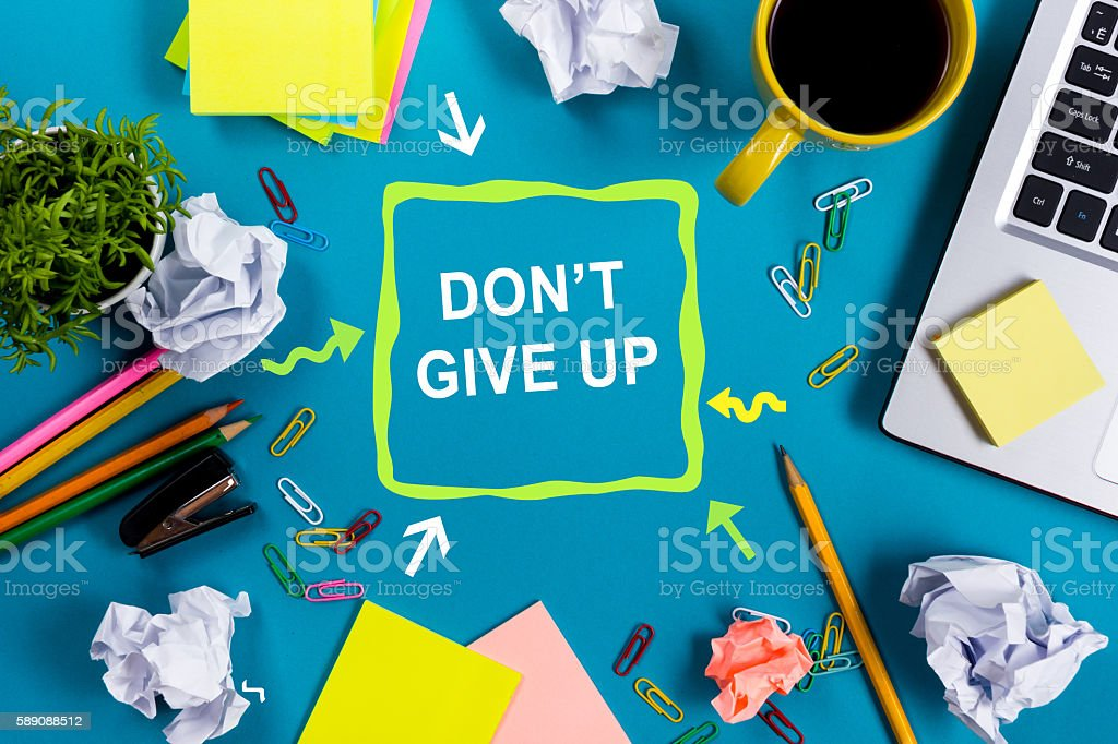 Don't give up. Office table desk with supplies, white stock photo