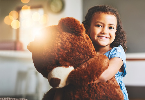 Portrait of a little girl holding her teddy bear at home